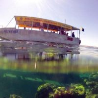 Underwater Split shot of Glass Bottom Boat and Coral at Ningaloo Reef