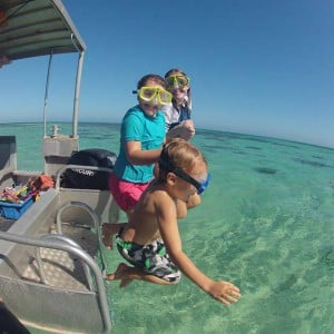 Kids jumping off Glass Bottom Boat with Snorkel Gear having fun